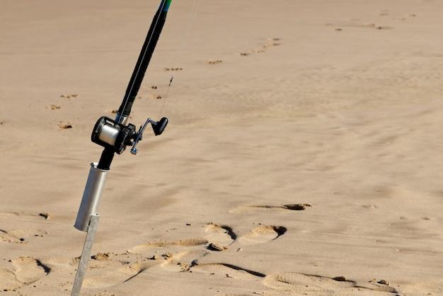 Closeup tiro de uma vara de pescar em uma superfície arenosa