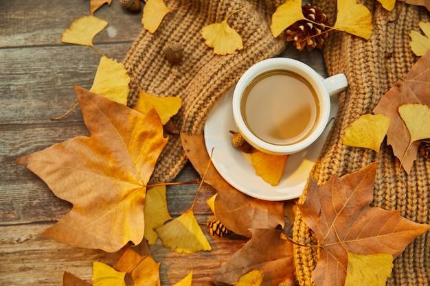 Closeup tiro de uma xícara de café e folhas de outono na superfície de madeira