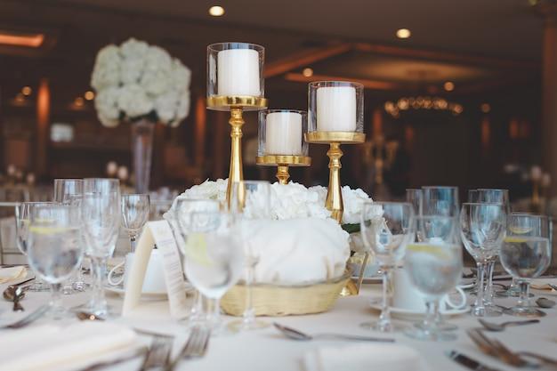 Closeup tiro de velas de pilar branco em candelabros em uma mesa de casamento