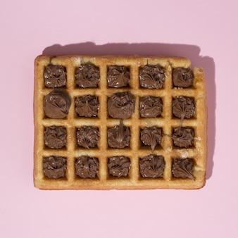 Closeup tiro de waffles caseiros com chocolate em uma superfície rosa