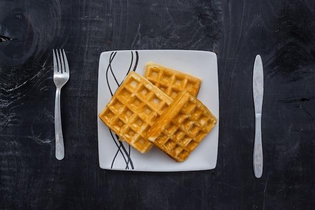 Closeup tiro de waffles quadrados em uma mesa de madeira