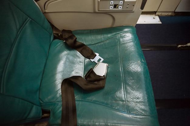 Closeup tiro do cinto desamarrado no assento do avião Foto Premium