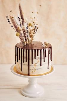 Closeup tiro do delicioso bolo boho com gotas de chocolate e flores no topo com enfeites dourados