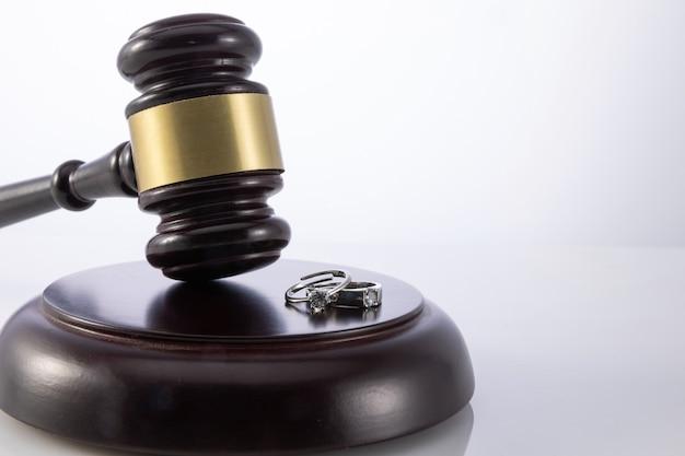 Closeup tiro do martelo do juiz com anéis de casamento - conceito de divórcio