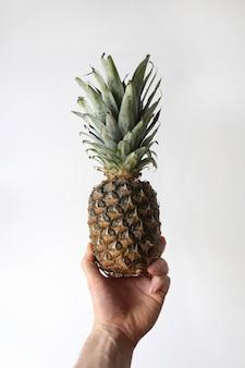 Closeup tiro vertical do braço de uma pessoa segurando um abacaxi na mão em um fundo branco