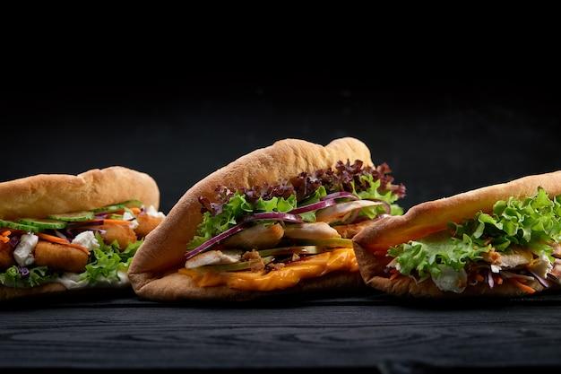 Closeup três diferentes apetitosos sanduíches ou hambúrgueres em fundo de madeira