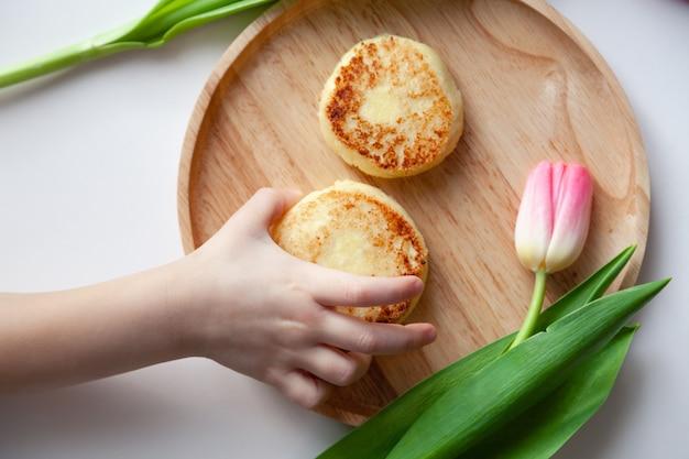 Closeup tulipa rosa fresca perto de prato redondo de madeira, a mão da criança leva dois cheesecakes fritos mordidos de ouro.