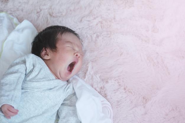 Closeup um bebê bocejando na cama com espaço de cópia