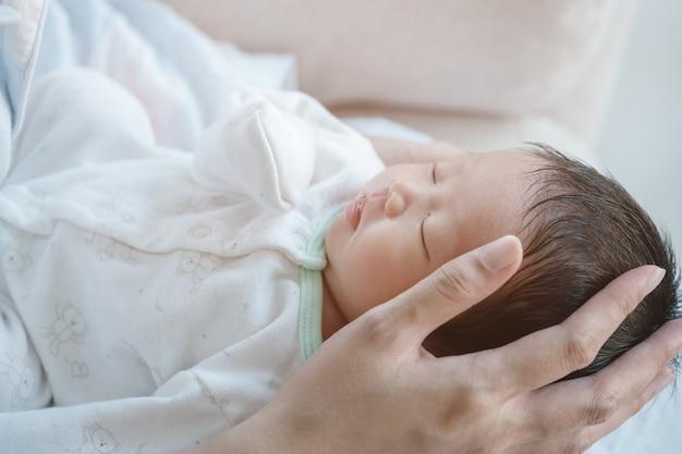 Closeup um bebê dormindo confortavelmente nos braços da mãe