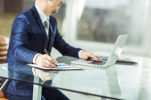 Closeup - um empresário de sucesso trabalhando em um laptop com dados financeiros no local de trabalho em um escritório moderno. a foto tem um espaço vazio para o seu texto