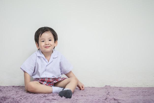 Closeup um garotinho no uniforme do estudante com sorriso rosto sente-se no tapete e parede branca texturizada