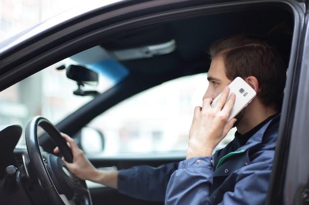 Closeup. um homem de sucesso falando ao celular no carro