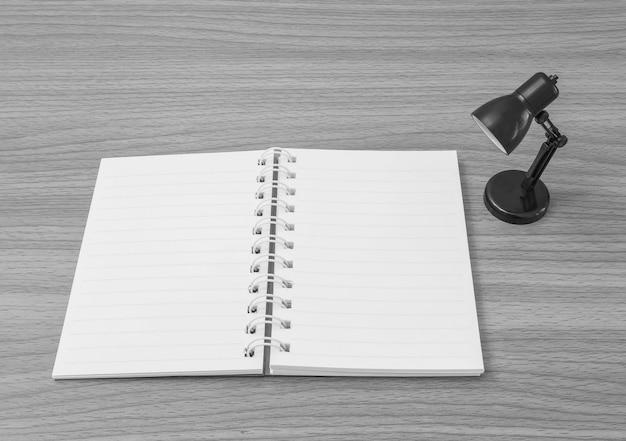 Closeup um livro de nota com pequena lâmpada na mesa