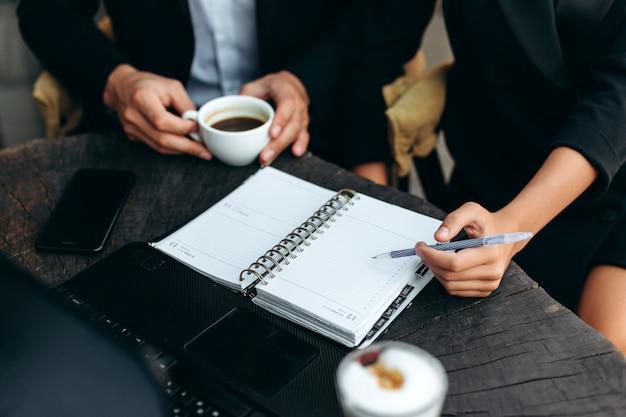 Closeup um planejador de papel. feminino mão segurando uma caneta e aponte para a folha.