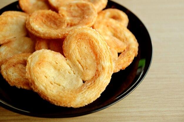 Closeup um prato de pastelaria francesa palmier na mesa de madeira
