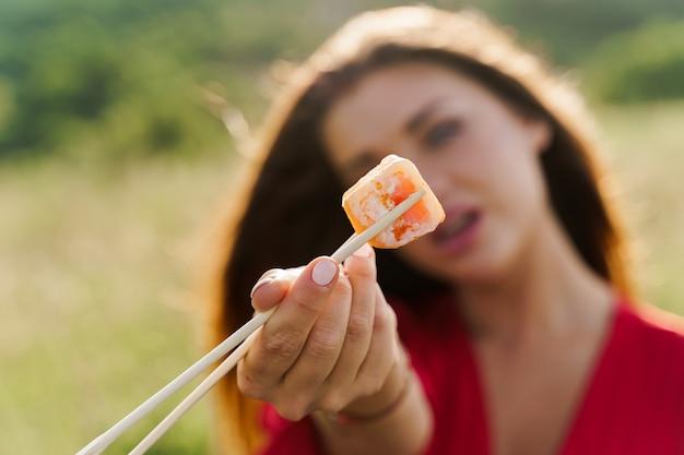 Closeup um sushi. garota atraente segura sushi com os pauzinhos nas mãos e dá para você. courier entregou sushi definido para uma linda mulher. caixa preta com sushi, wasabi, gengibre.