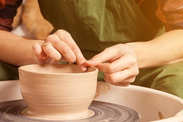 Closeup uma ceramista com uma camisa xadrez e um avental verde esculpe lindamente uma tigela profunda de argila marrom