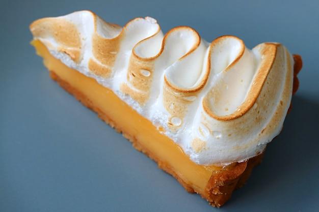 Closeup uma fatia de saborosa tarte de limão e merengue no prato azul