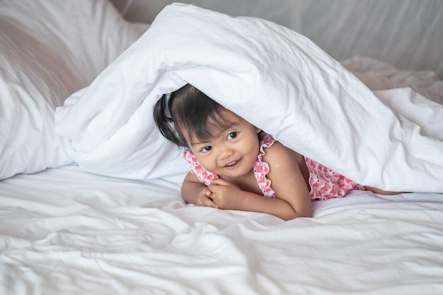 Closeup uma garotinha mentira na cama sob o cobertor com sorriso rosto de manhã