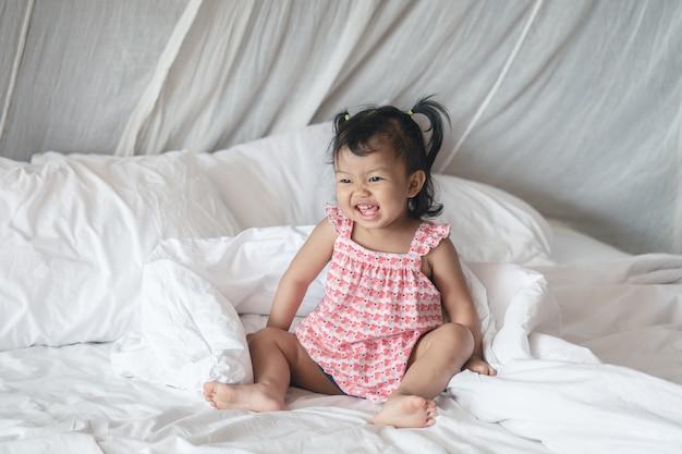 Closeup uma menina sente-se na cama com sorriso rosto de manhã