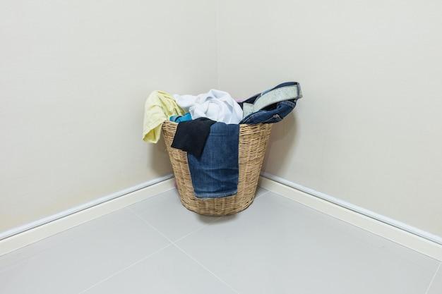 Closeup usado roupas na cesta de madeira no canto da sala