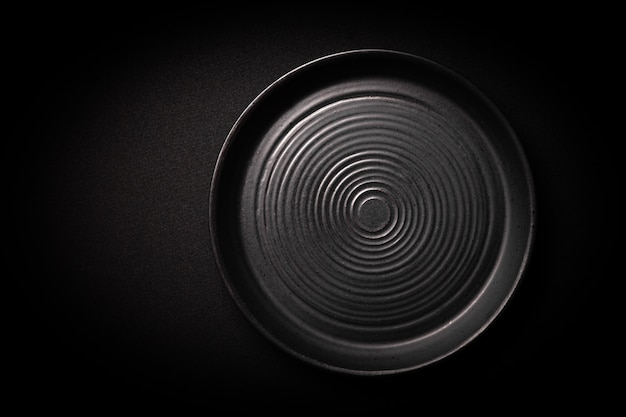 Closeup vazia redonda placa cerâmica preta sobre fundo escuro