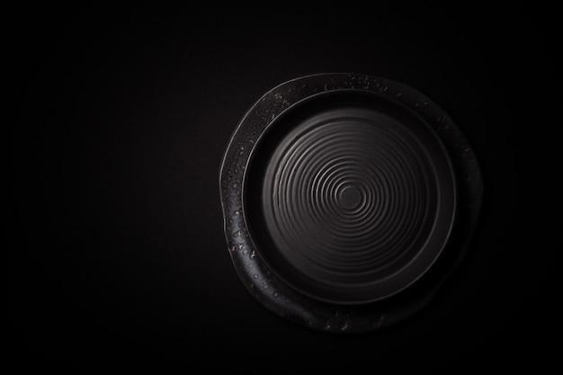 Closeup vazias redondas placas cerâmicas pretas sobre fundo escuro, com espaço de cópia