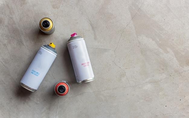 Closeup velhas latas de tinta spray no chão de cimento