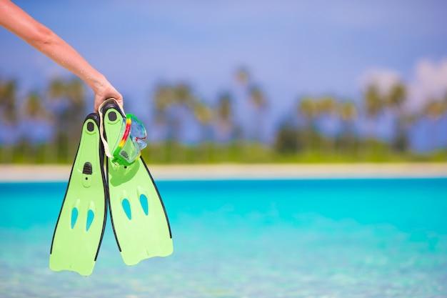 Closeup verde barbatanas em uma mão feminina na praia branca