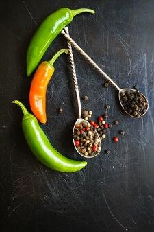 Closeup verde malagueta e diferentes tipos de grãos de pimenta