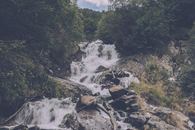 Closeup vista cachoeira nas montanhas, parque nacional de dombay, cáucaso, rússia. paisagem de verão, clima ensolarado e dia ensolarado