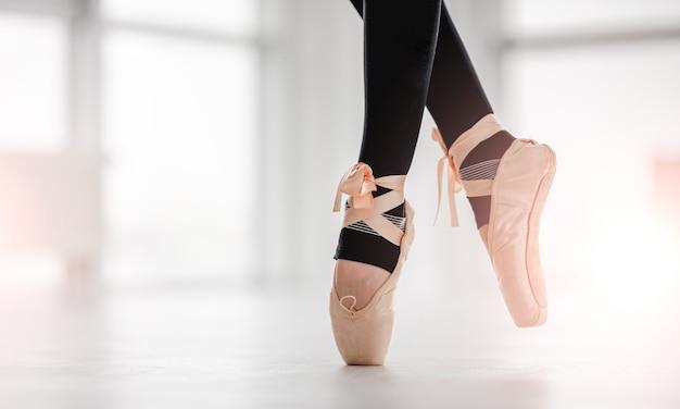 Closeup vista com belas pernas de bailarina usando leggings pretas e sapatilhas de ponta bege, ficando na ponta dos pés no ensolarado estúdio de dança