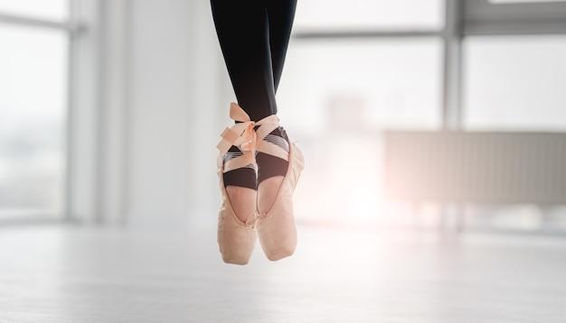 Closeup vista com pés de bailarina na ponta dos pés durante a aula de dança de balé em um estúdio ensolarado com janelas