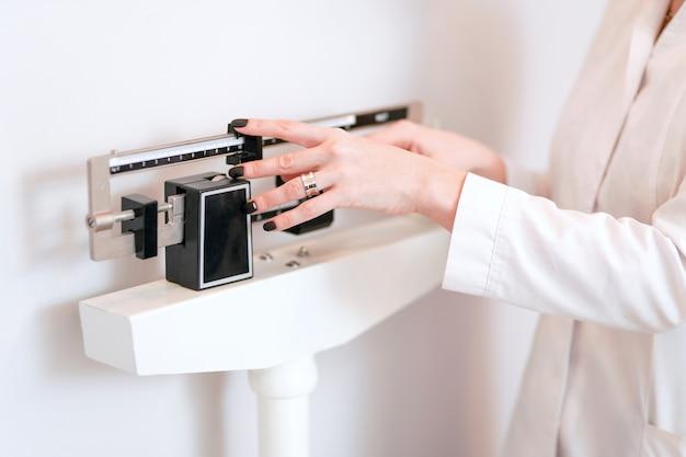 Closeup vista da mão da mulher, ajustando a escala de peso de equilíbrio profissional