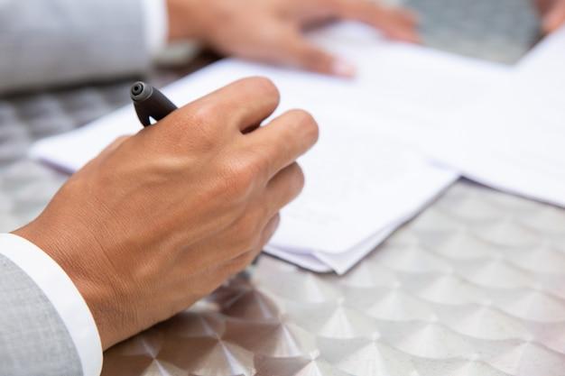 Closeup vista da mão masculina, segurando a caneta