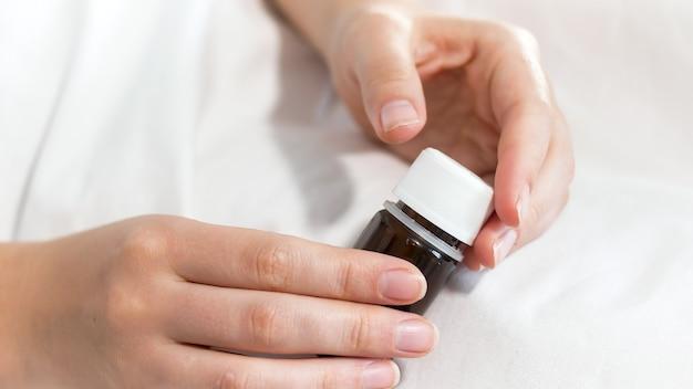 Closeup vista da paciente do sexo feminino segurando o frasco com medicamentos e comprimidos na mão.
