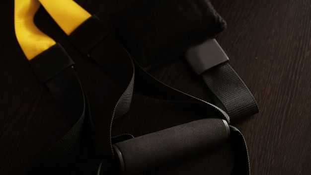 Closeup vista da suspensão em fundo de madeira preta, treinamento em casa - fitness em casa