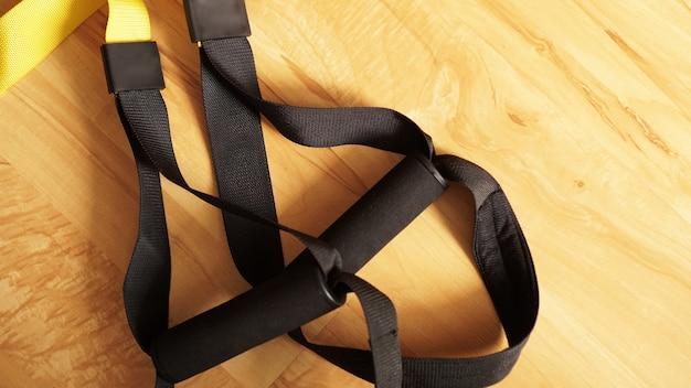 Closeup vista da suspensão no treinamento de fundo de madeira em casa - fitness em casa