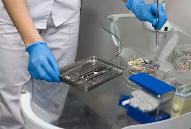 Closeup vista das mãos do dentista segurando instrumentos odontológicos e materiais consumíveis