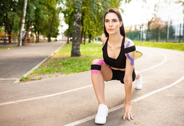 Closeup vista de bruette mulher flexível com corpo musculoso aquecendo ao ar livre