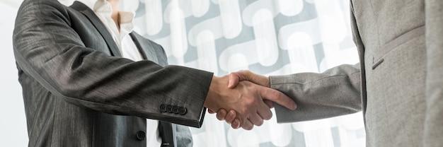 Closeup vista de homem de negócios e mulher apertando as mãos em saudação ou acordo. imagem de visão ampla.