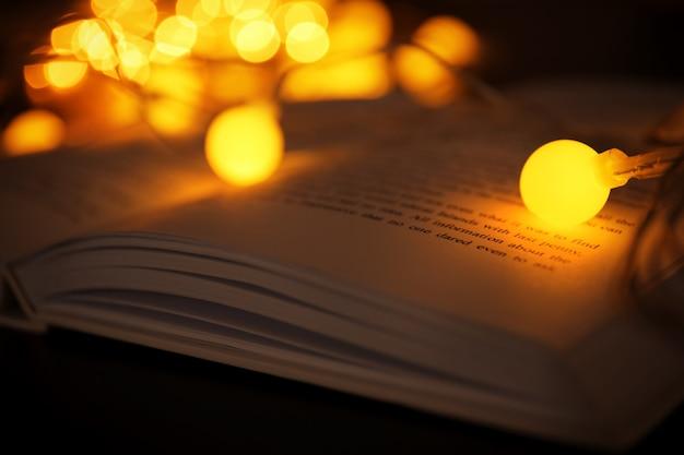 Closeup vista de livro aberto e bela guirlanda contra luzes desfocadas
