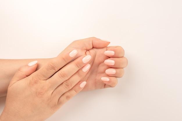 Closeup vista de mulher com belas mãos em fundo branco, espaço para texto. tratamento de spa. vista superior das mãos femininas preparadas com manicure pastel no fundo rosa. vista do topo