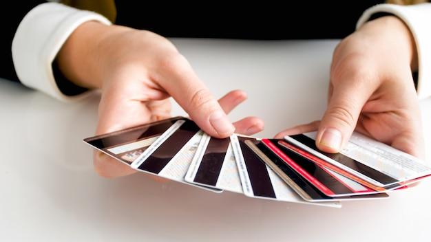 Closeup vista de mulher segurando cartões de crédito bancários de plástico nas mãos.