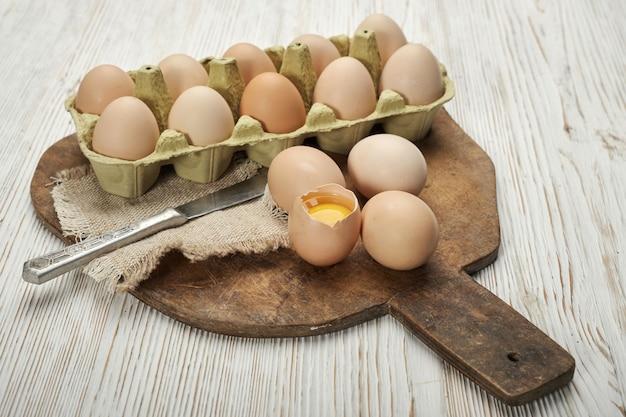 Closeup vista de ovos de galinha crus em caixa de ovo em fundo de madeira