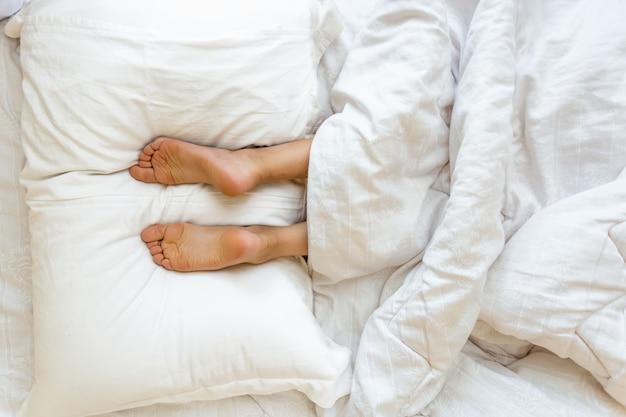 Closeup vista de pés apoiados em um travesseiro branco macio na cama