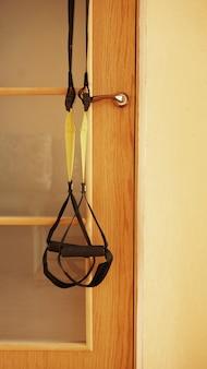Closeup vista de suspensão na porta em fundo de madeira, treinamento em casa - fitness em casa