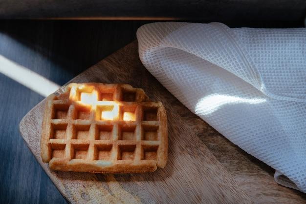 Closeup vista de um artesão fazendo waffles em uma mesa de madeira