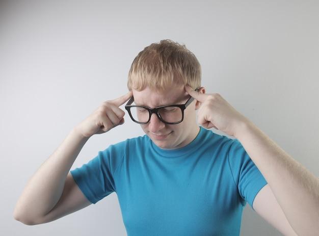 Closeup vista de um homem caucasiano vestindo uma camiseta azul e óculos fazendo gestos engraçados