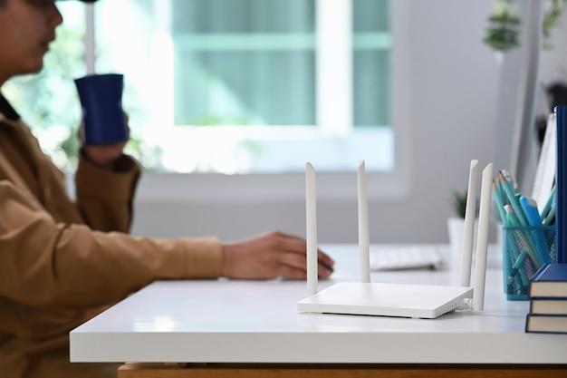 Closeup vista de um roteador sem fio com jovem usando o computador laptop em segundo plano.